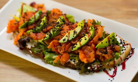 Image of salmon toast with lettuce, avocado and cheese on the plate indoors.