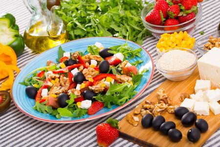 Set of ingredients and ready-made salad with rocket, vegetables and feta cheese on striped background Stock Photo