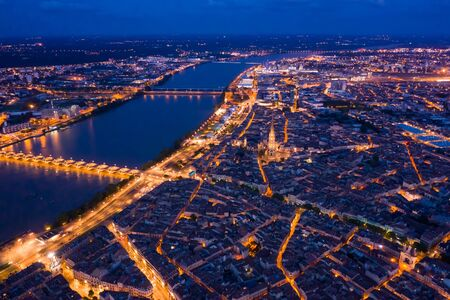 Picturesque view from drone of illuminated modern cityscape of French port city of Bordeaux on river Garonne and Stone Bridge Banque d'images