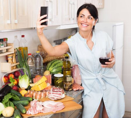 Adult woman is taking selfie by phone in time cooking on the kitchen in home.
