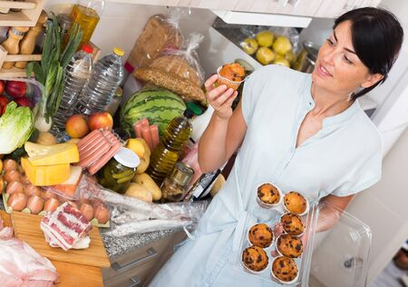 Portrait of female who is standing with cupcakes on kitchen at home.