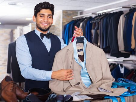 Male client demonstrating his choice of suit in apparel store
