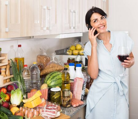 Adult american female is calling her mother for talking about cooking at home. Stock fotó
