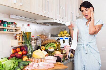 Young woman is upset of check on food in kitchen at home