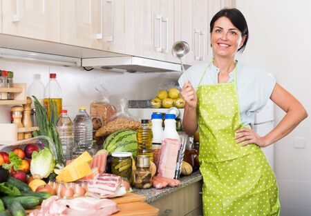 Portrait of female who is standing on kitchen at home.