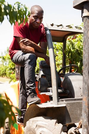 Portrait of adult Afro male driver working on forklift in fruit warehouse