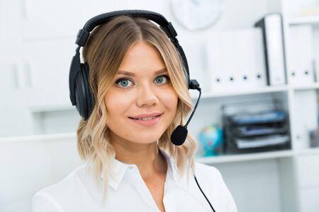 Ragazza nella call center con le cuffie che si siedono con il computer portatile