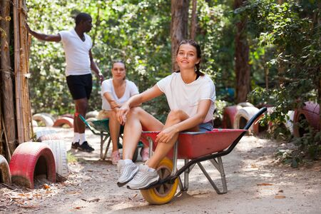 Competitions in amusement park - who will quickly bring girl in the garden wheelbarrow Stock Photo - 134595940