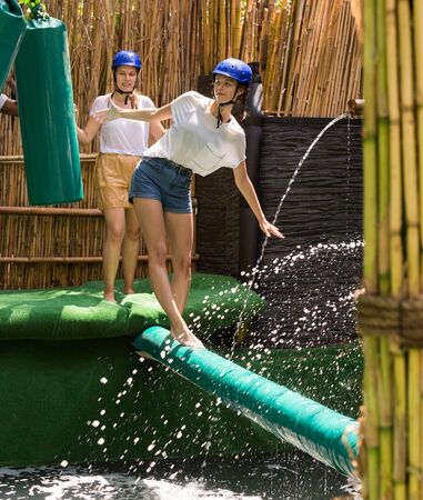 Excited men and women passing crossbar with obstacles under water in adventure park
