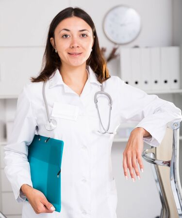 Young woman medic in white uniform holding clipboard in clinic's office