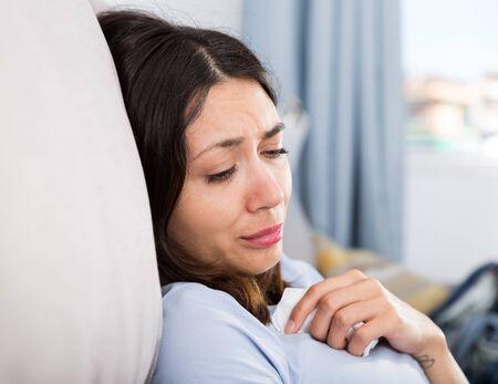 Portret van trieste jonge vrouw die op de bank in het interieur denkt Stockfoto