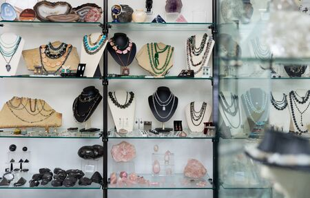 View of window of jewelry store offering various adornments from natural gemstones for sale