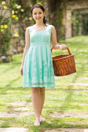 portrait of young happy russian  woman holding a basket  near roses in a garden