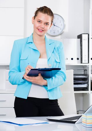 Manager woman is signing contract at office.