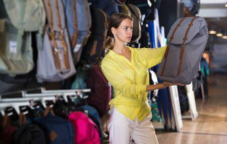 Attractive girl choosing backpack in apparel showroom