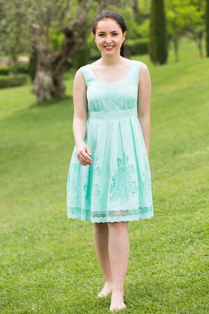 portrait of young cheerful european female in  dress  near roses in a outdoors