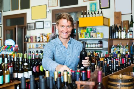 cheerful smiling man customer picking bottle of wine in wine store