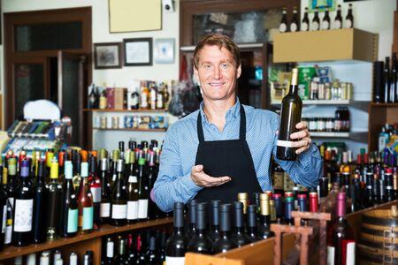 Positive seller man in apron promoting bottle of wine in wine store