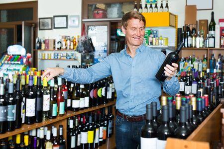 cheerful man customer picking bottle of wine in wine store