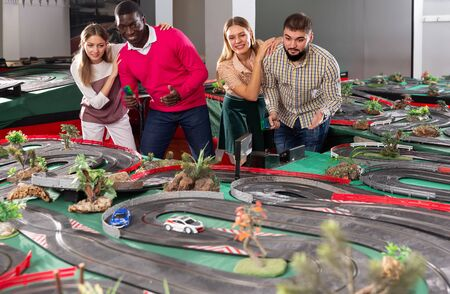 Two teams from couples play slot car racing game