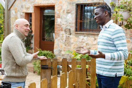 Good neighbors talk on the border of their farms Stock fotó