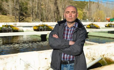 Portrait of confident male owner of trout farm standing arms crossed near open fish tanks outdoors