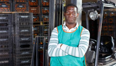 Adult African worker and electric lift truck in warehouse with containers of tangerines