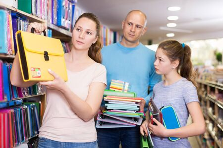 Loving young  parents with daughter buying school supplies in stationery store