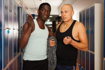 Two athletes in the locker room after training
