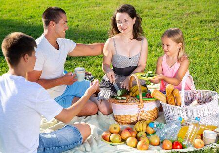 Glückliche junge Frau mit ihrem Mann und zwei Kindern, die zusammen Picknick auf der grünen Wiese genießen