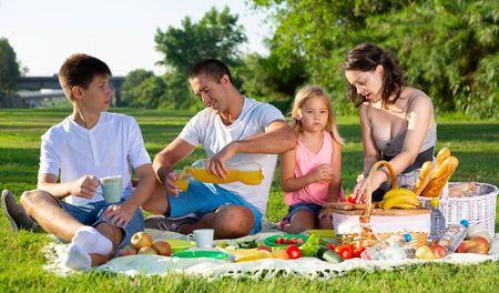 Heureux parents avec deux enfants en train de pique-niquer ensemble sur un pré vert dans un parc