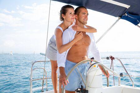 Hombre y mujer joven conduciendo un yate de placer, disfrutando de un romántico viaje por mar en un cálido día de verano Foto de archivo