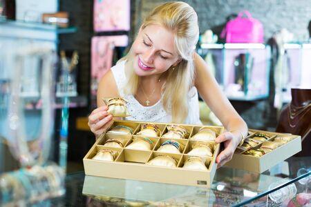 Froher Verkäufer, der Armbänder im Zubehör- und Bijouterie-Laden ausstellt Standard-Bild