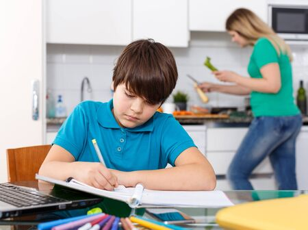 Positive schoolboy doing homework using laptop at kitchen interior, woman cooking at background