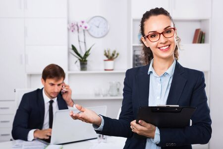 Glad positive business female secretary having cardboard in hands and working in office
