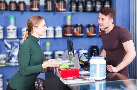 Chica atlética comprando complementos alimenticios deportivos en la tienda, consultando con el vendedor. Centrarse en la mujer