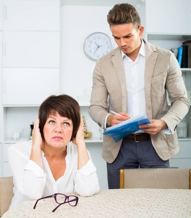 Adult woman has discontentedly turned away from man who suggests her to sign documents