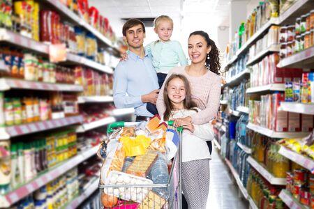 Familia amistosa con dos hijas de compras en el supermercado local.