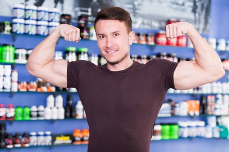 Cheerful athletic guy showing biceps in shop interior