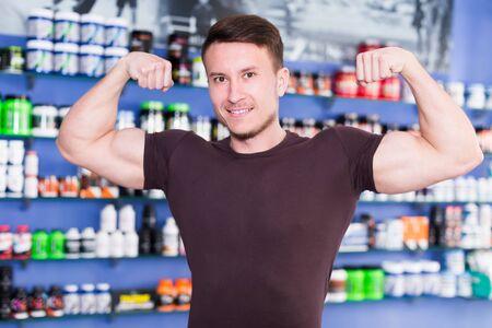 Wesoły wysportowany facet pokazujący bicepsy we wnętrzu sklepu