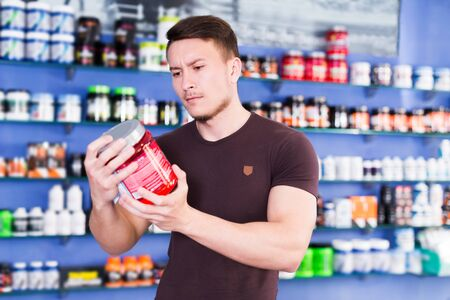 young guy looking for necessary food supplements in sport nutrition store Foto de archivo - 135024516