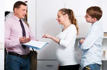 Positive middle-aged mother and son meeting with social worker indoors Stock fotó