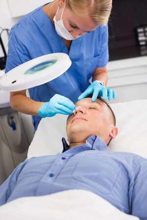 Woman specialist is cleaning skin of patient with using magnification before the procedure in clinic. Stock Photo