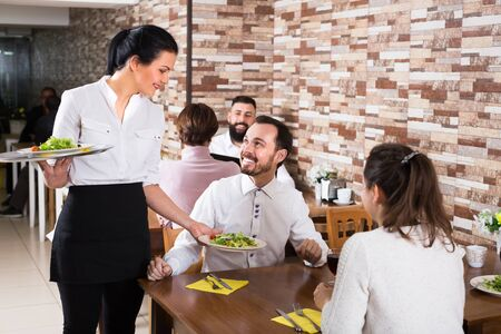 Portrait of chatting adults in restaurant and cheerful waitress