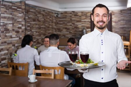 friendly waiter taking care of adults guest at cafe table