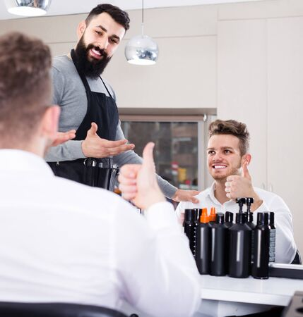 Young male hairdresser showing resulting haircut to client at hair salon