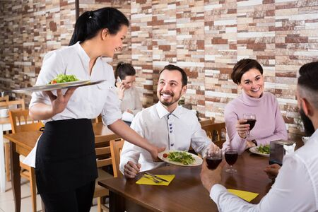 Portrait of chatting adults in restaurant and smiling waitress