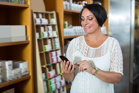Mature woman texting using her phone in healthy food store