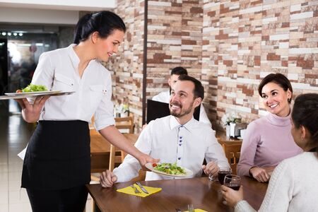 Young girl waitress serving meal for restaurant guests at table