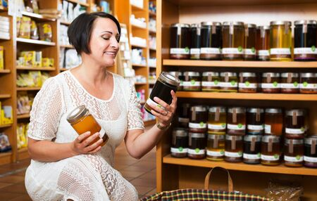 Portrait of positive mature woman with different kinds of natural honey in healthy food store